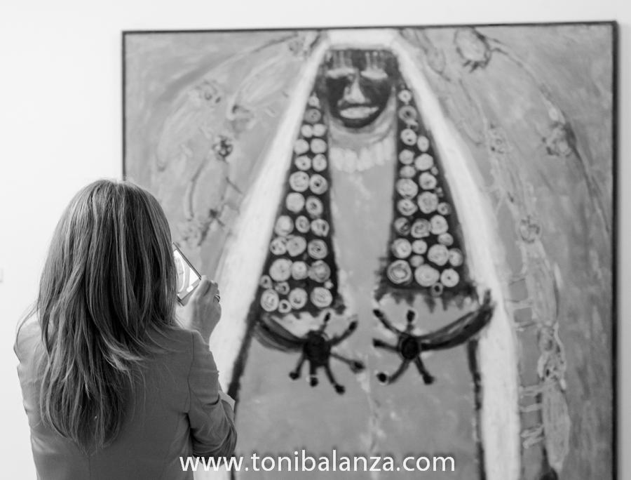 Una visitante a la exposición de Enric Alfons en la Universidad de Alicante,  fotografía una de las pinturas con un teléfono móvil. Fotografía de Toni Balanzà