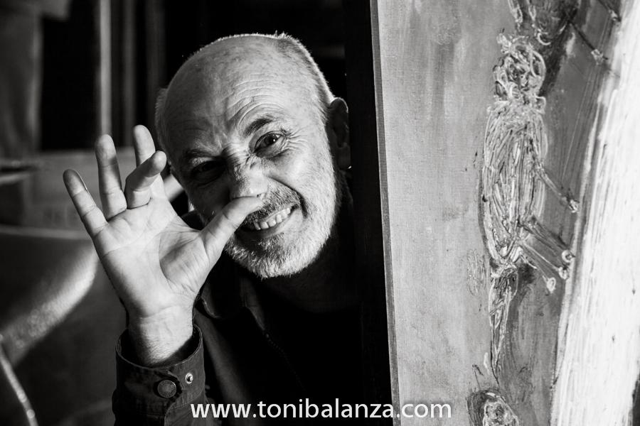 Retrato del pintor Enric Alfons por Toni Balanzà, en blanco y negro, escondido tras sus pinturas. Fotografía de Toni Balanzà