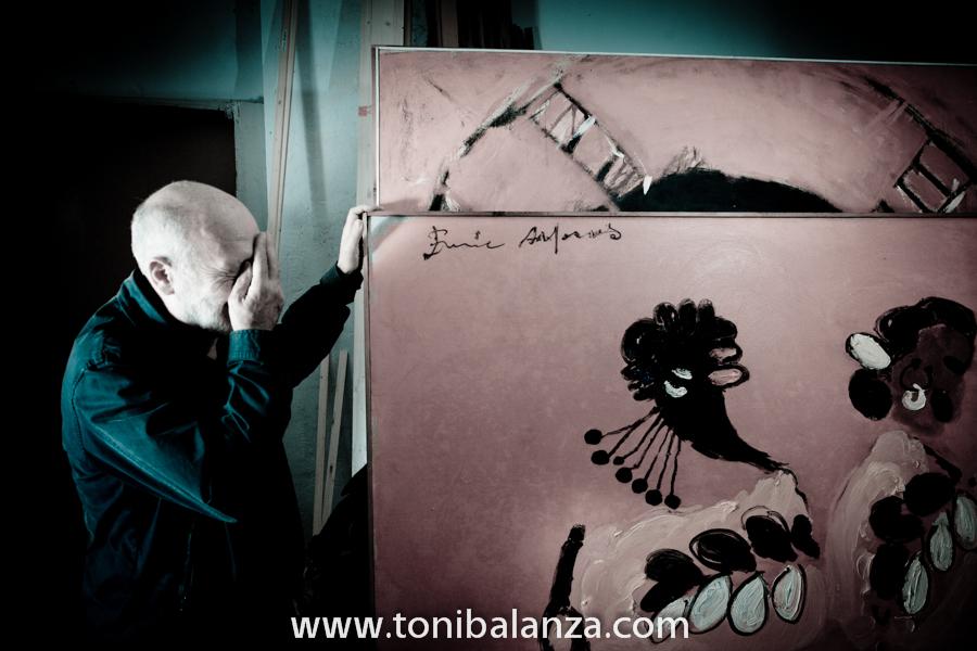 El pintor Enric Alfons, se tapa la cara a modeo de máscara con su propia mano, junto a una de sus obras en Valencia. Fotografía de Toni Balanzà