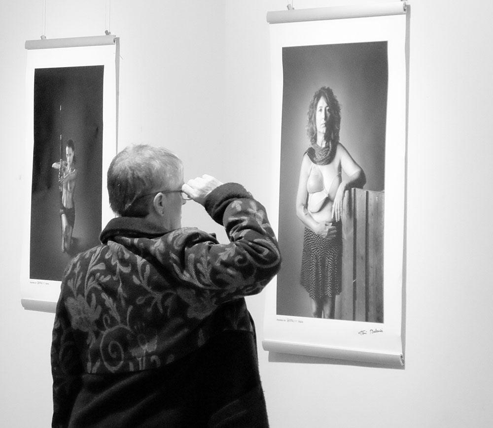 Mujer observa la fotografía de mujer mastectomizada