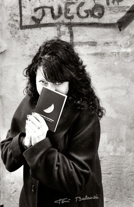 La escritora i poeta Estel Julià sujeta uno de sus libros en una fotografía de Toni Balanzà