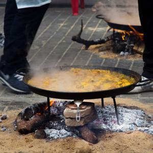 Concurso de paellas en Fallas - Si hay algo típico en fallas, es el concurso de paellas. Plato gastronómico de fama mundial, que cada uno lo prepara, con sus mejores artes culinarias. El el detalle se aprecia, los malabares y equilibrios a los que se somete a la paella sobre el triángulo de hierro, para que el caldo esté a nivel.