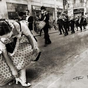 Instantes de un pasacalle en fallas - Mi amiga Esther López, ajustándose un calcetín con la banda de Música SIOAM de Benimàmet desfilando por detrás.