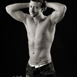 Javier retrato modelo masculino torso desnudo blanco y negro - Retrato de Javier, modelo masculino, contrata una sesión de desnudo masculino en blanco y negro. Sesión fotográfica para regalar a su pareja una fotografía sensual y erótica. Músculos tatuados, pectorales definidos, imagen sexy de un chico guapo.