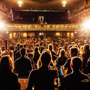 teatro olympia valencia banda musica juvenil sioam - Reportaje fotográfico a la Banda Juvenil SIOAM de Benimàmet en el Teatro Olympia de Valencia. Fotografía desde el fondo del escenario, contraplano de los músicos frente al público aplaudiendo.